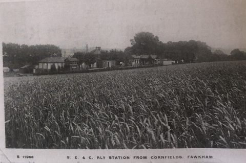 old postcard showing a cornfield and distant view of a station