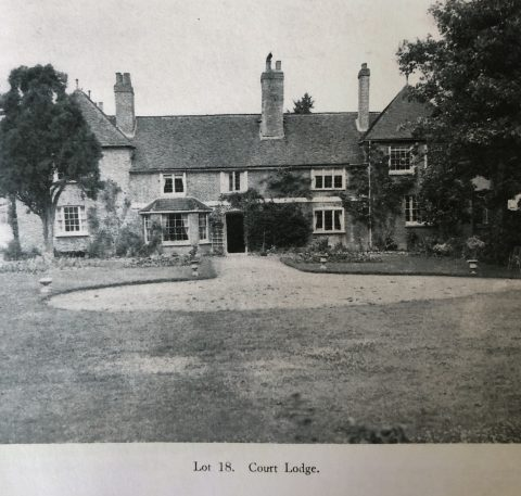 old photo showing a house with tall chimneys