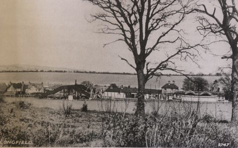 postcard showing a tree and a distant view of a railway station