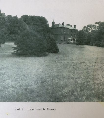 an old photo showing a grand house with a large lawn