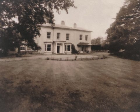 old photo showing a large White House and a lawn