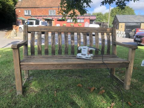photo of wooden bench sanded back with sander placed on it