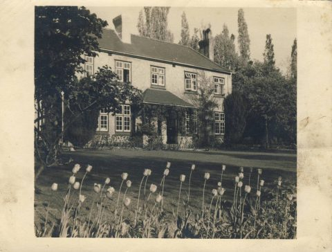 photo of a house with a lawn in front, and flower