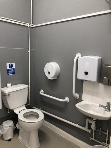 disabled toilet facility with grey walls and white grab handles