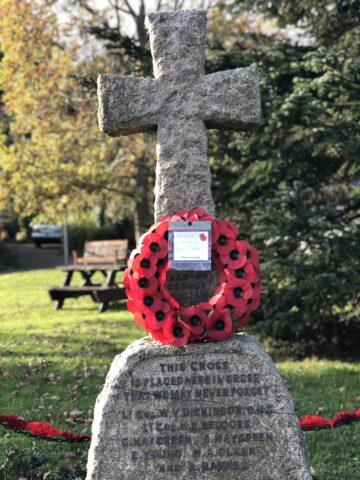 War memorial stone cross with poppy wreath