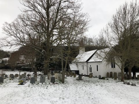white church and graveyard in the snow